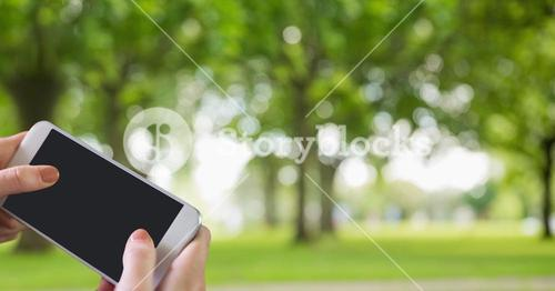 Hands using smart phone with blank screen against park