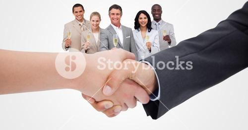 Cropped image of business people doing handshake with employees holding champagne in background