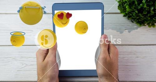 Hands holding tablet PC while emojis flying over table