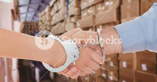 Digital composite image of business people in handcuffs shaking hands in warehouse