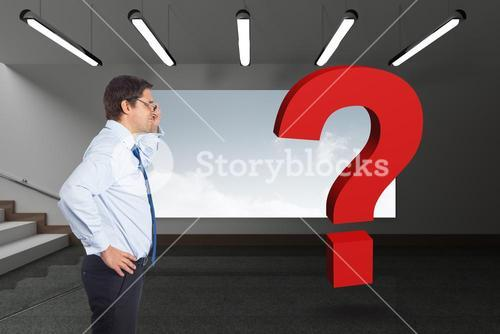 Digital composite image of businessman looking at red question mark
