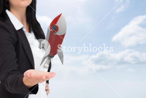 Digital composite image of businesswoman with rocket in sky