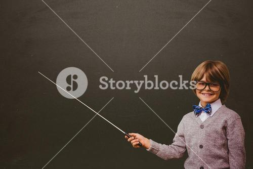 Cute student holding stick against black board