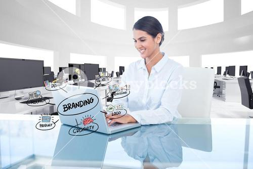 Businesswoman working on laptop with branding sign and icons over desk