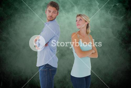 Couple with arms crossed arguing over green background