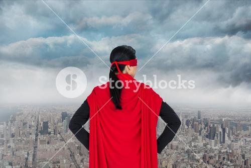 Businesswoman in super hero costume looking at buildings