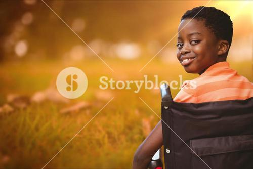 Boy smiling while sitting in wheelchair at park