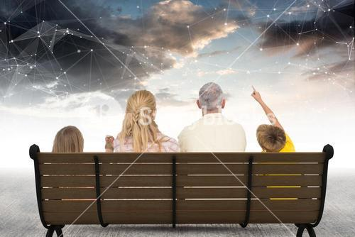 Rear view of family sitting on bench against star constellations