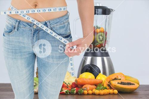 Midsection of woman measuring waist with juicer and fruits in background