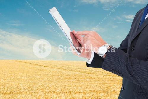 Midsection of businessman using tablet PC at farm