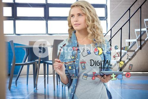 Businesswoman holding tablet PC surrounded by digital marketing text and icons