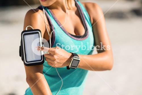Midsection of woman using smartphone on armband
