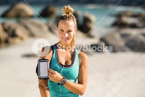 Young woman touching smartphone on armband