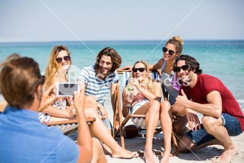 Man photographing cheerful friends at beach