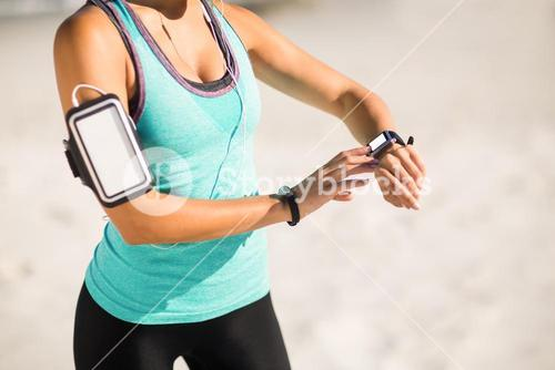 Woman using smart watch at beach