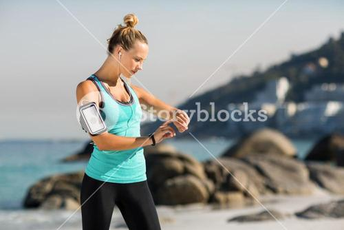 Woman with smartphone on armband listening music