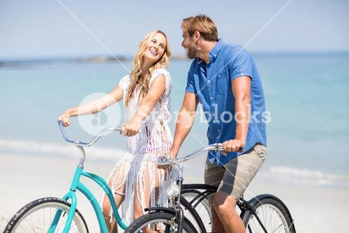Couple riding bicycles at beach