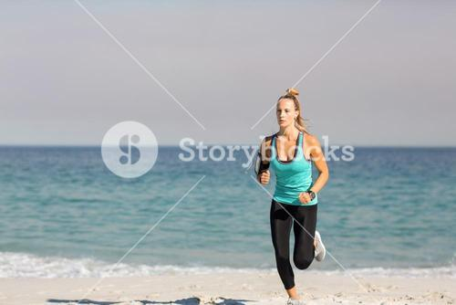 Young woman jogging on shore at beach