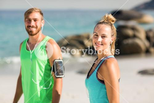 Happy couple in sports clothing standing at beach