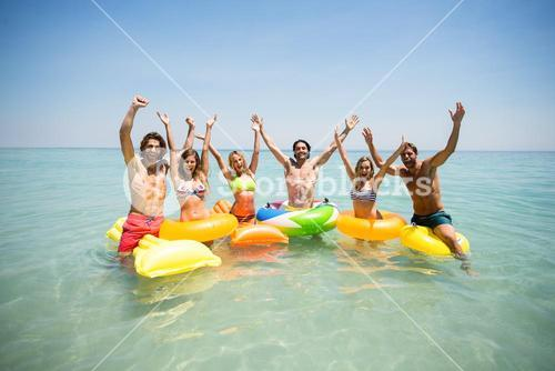 Friends enjoying on inflatable rings and pool rafts in sea