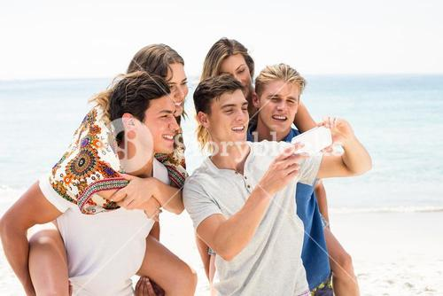 Friends looking in mobile phone at beach