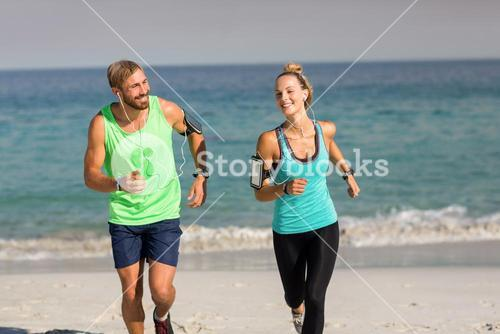 Young couple smiling while jogging