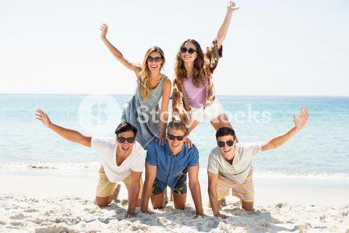 Friends forming pyramid with arms raised at beach