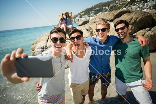 Male friends taking selfie at beach