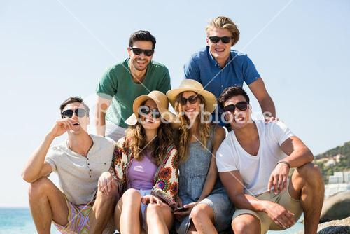 Young smiling friends against clear sky