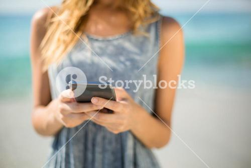 Midsection of woman using mobile phone at beach