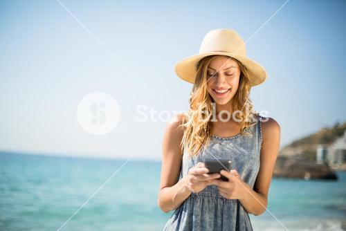 Woman smiling while using mobile phone at beach