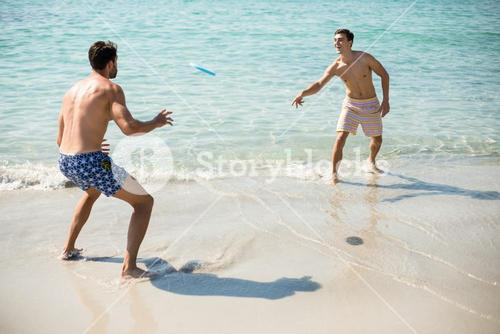Male friends playing frisbee on shore at beach