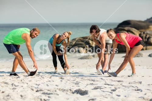 Friends stretching on shore at beach