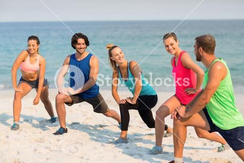 Happy friends stretching on shore at beach