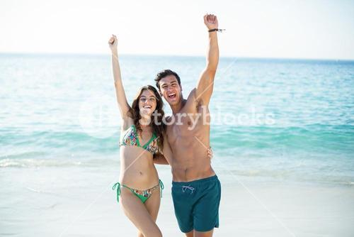 Couple standing with arms raised at beach