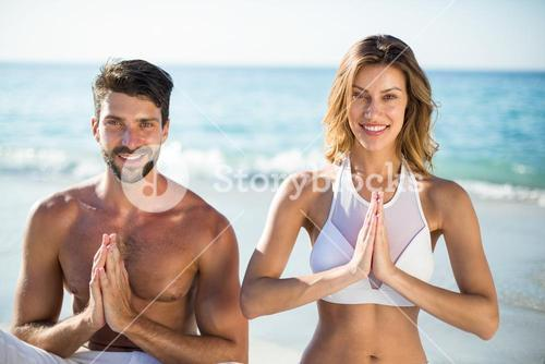 Portrait of young couple meditating while sitting on shore