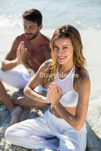 Happy woman meditating by boyfriend at beach