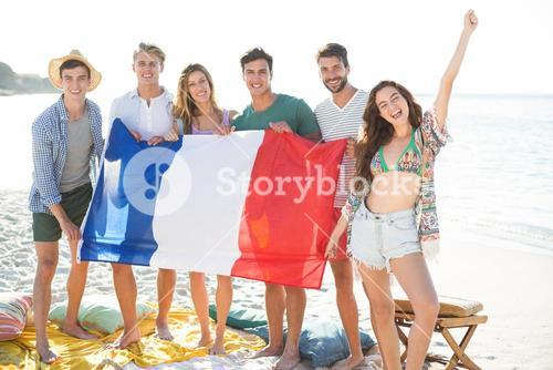 Friends holding French flag while standing at beach