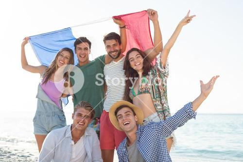 Friends holding French flag on shore at beach