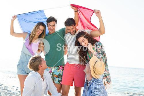 Happy friends holding French flag on shore