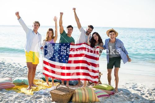 Friends holding American flag while standing on shore