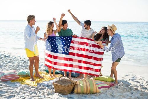 Friends holding American flag on shore at beach