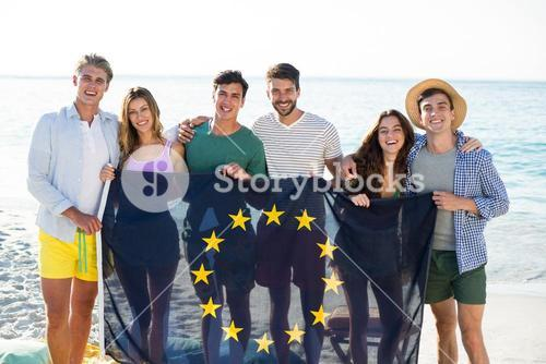 Friends holding European Union flag on shore at beach