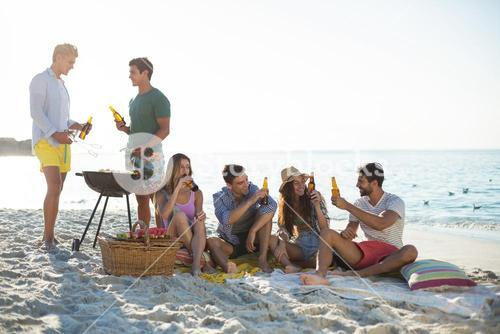 Friends having drinks by barbecue at beach against sky