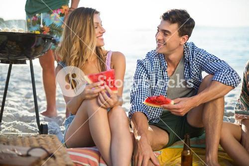 Friends having watermelon on shore at beach