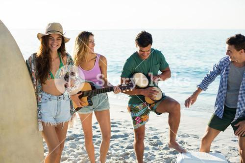Friends enjoying music while standing at beach