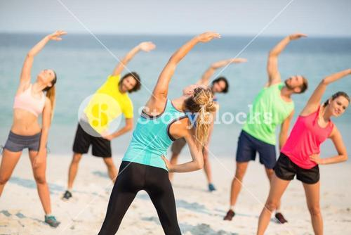Friends stretching while standing on shore