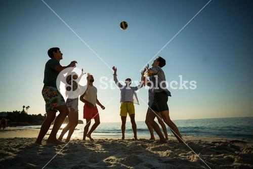 Friends playing volleyball on shore at beach