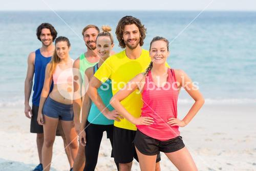 Happy friends in sports clothing standing at beach