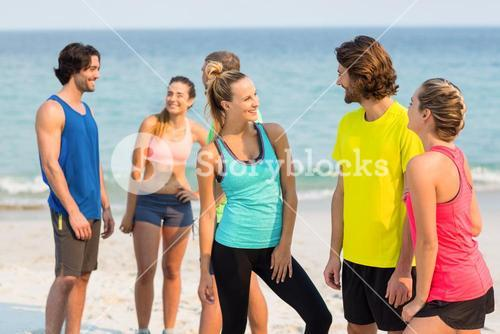 Friends in sports clothing talking while standing at beach